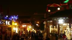Crowd pedestrian people Walk on China Beijing night market.Neon shop at HouHai. Stock Footage