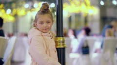 Young girl in white coat poses near decorative lamppost Stock Footage