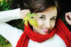 close-up portrait of an beautiful autumn woman laying on ground with leave in - stock photo