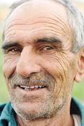 face portrait of a wrinkled cheerful smiling senior man - stock photo