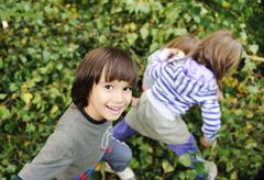 happy childhood outdoor, happy faces between the leaves of the trees in fores - stock photo
