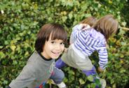 Stock Photo of happy childhood outdoor, happy faces between the leaves of the trees in fores
