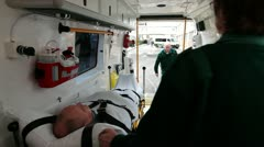 Ambulance staff unload patient on trolley Stock Footage
