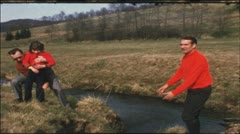Vintage 8 mm film: Fathers throws girl over creek Stock Footage