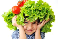 Kid with salad and tomato hat on his head, fake hair made of vegetables Stock Photos