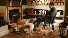 Man and his dog by log fire in country pub Stock Footage