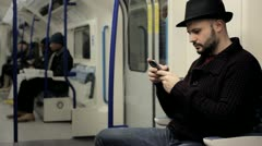 Man reading text messages on a mobile on a tube train Stock Footage