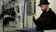 Stock Video Footage of man reading text messages on a mobile on a tube train