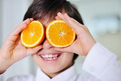 Little boy holding orange slices on eyes as sunglasses Stock Photos