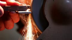 Worker sharpens metal piece on the abrasive machine 3 Stock Footage