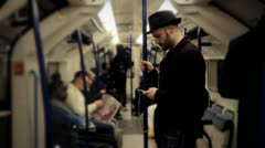 Man listening music on a tube train standing wider shot Stock Footage
