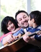 father and his children having good time at home - stock photo