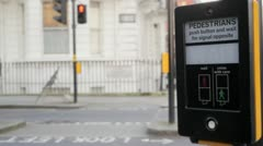 Pedestrian pushes button and waiting for the green sign at a crossing, London Stock Footage
