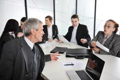 senior businessman at a meeting. group of colleagues in the background - stock photo