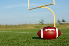 football with goal posts beyond - stock photo