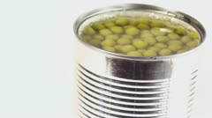 Many green peas rotates in metal tin isolated on white Stock Footage