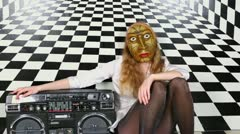 Sexy girl in mask sits near old tape cassette recorder Stock Footage