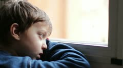 Child sad and lonely looking through window Stock Footage