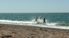 Group of children run at the beach and dive into the sea - stock footage