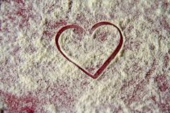Red heart shape in flour Stock Photos
