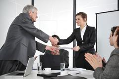 Business partners handshaking at meeting and receiving applause Stock Photos