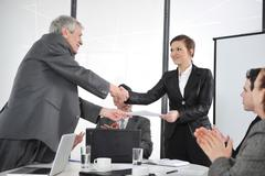 Happy business leaders handshaking at meeting Stock Photos
