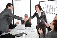 Stock Photo of business partners shaking hands after making deal while their co-workers appl