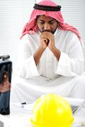 arabic engineer having a concern about the plans - stock photo