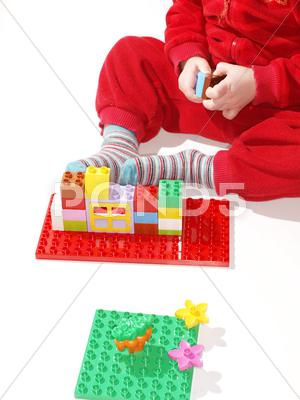 Stock photo of unrecognizable kid in red, playing