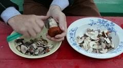 Man hands clean orange-cap mushrooms knife on wooden table Stock Footage