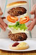 Levitating zero gravity burger in hands Stock Photos