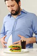 Fat man concerns about fast junk food Stock Photos