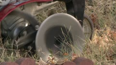 Stock Footage Close up of Rototiller blades churning dirt in a garden farm Stock Footage