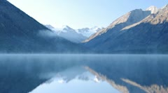 Beautiful mountain range with snow on the peak are reflected in foggy lake Stock Footage