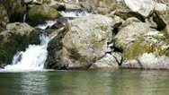 Stock Video Footage of Mountain river flowing down through the rocks shooted with a slow up tilt