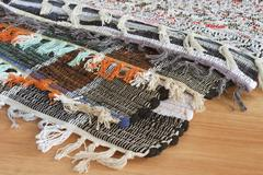 Homespun mat of colored ribbons Stock Photos