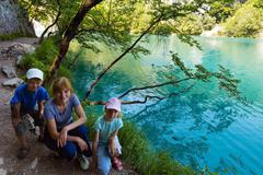 family near summer azure  limpid  transparent lake (plitvice, croatia) - stock photo