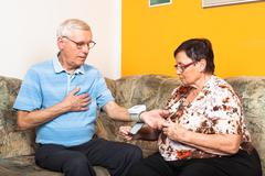Seniors measuring blood pressure Stock Photos
