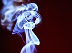 abstract blue smoke against a dark background - stock photo