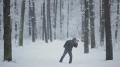 The young man-photographer walkink in the winter forest, snowfall weather Stock Footage