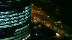 Traffic near large office building, view from above at night Stock Footage