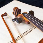 Fiddle bow and scroll on music book Stock Photos