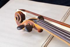 violin bow and scroll on music book - stock photo