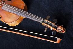 Fiddle pegbox and bow on black velvet Stock Photos