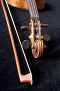 Fiddle scroll and bow on black velvet Stock Photos