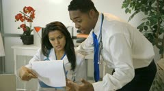 Doctors going over some paperwork in an office Stock Footage