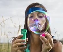 Face of woman that blows soap bubbles Stock Photos