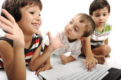 Group of children playing on white laptop together. isolated on white. Stock Photos