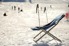 Empty chair, full resort, european mountains, winter vacation Stock Photos