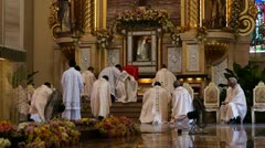 Priests kneeling in front of the altar - stock footage